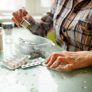 non autosufficienza: donna anziana che prende medicine